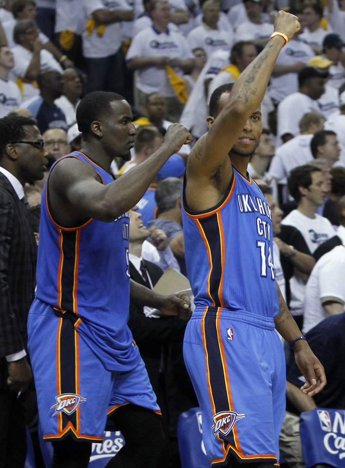 Photo - Oklahoma City Thunder players Kendrick Perkins, left, and Daequan Cook (14) celebrate in the final moments of the third overtime period of Game 4 against the Memphis Grizzlies in a second-round NBA basketball playoff series on Tuesday, May 10, 2011, in Memphis, Tenn. Oklahoma City won 133-123 in triple overtime. (AP Photo/Lance Murphey)