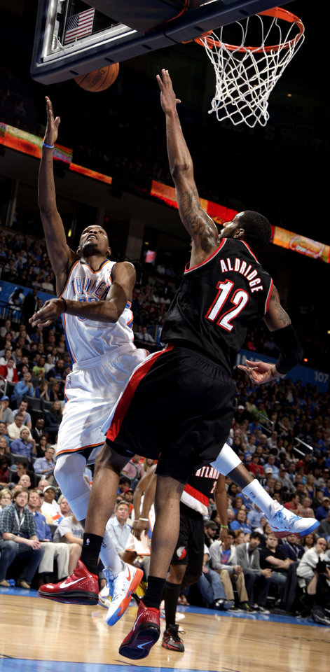 Oklahoma City\'s Kevin Durant (35) shoots a lay up as Portland \'s LaMarcus Aldridge (12) defends during the NBA basketball game between the Oklahoma City Thunder and the Portland Trailblazers at Chesapeake Energy Arena in Oklahoma City, Sunday, March 18, 2012. Photo by Sarah Phipps, The Oklahoman.