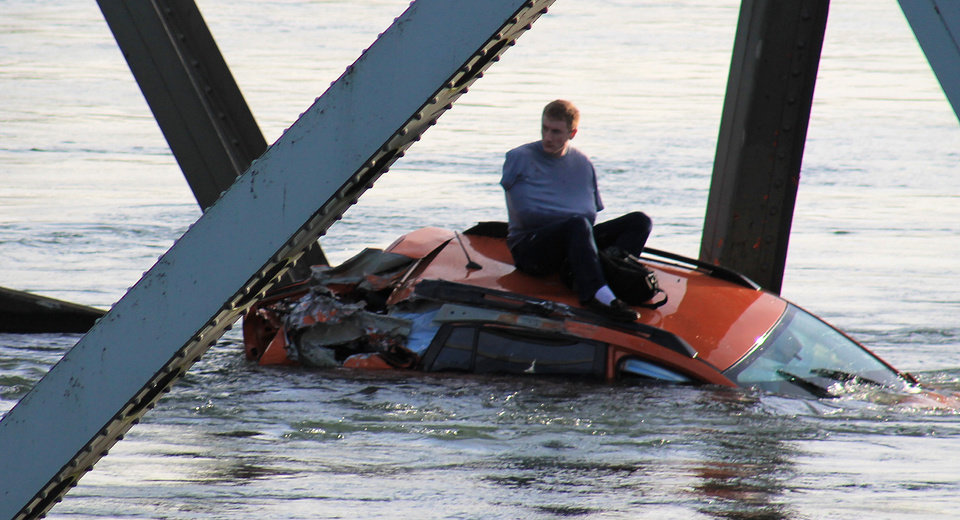 Photo - In this photo provided by Francisco Rodriguez, a man is seen sitting atop a car that fell into the Skagit River after the collapse of the Interstate 5 bridge there minutes earlier Thursday, May 23, 2013, in Mount Vernon, Wash. (AP Photo/Francisco Rodriguez)