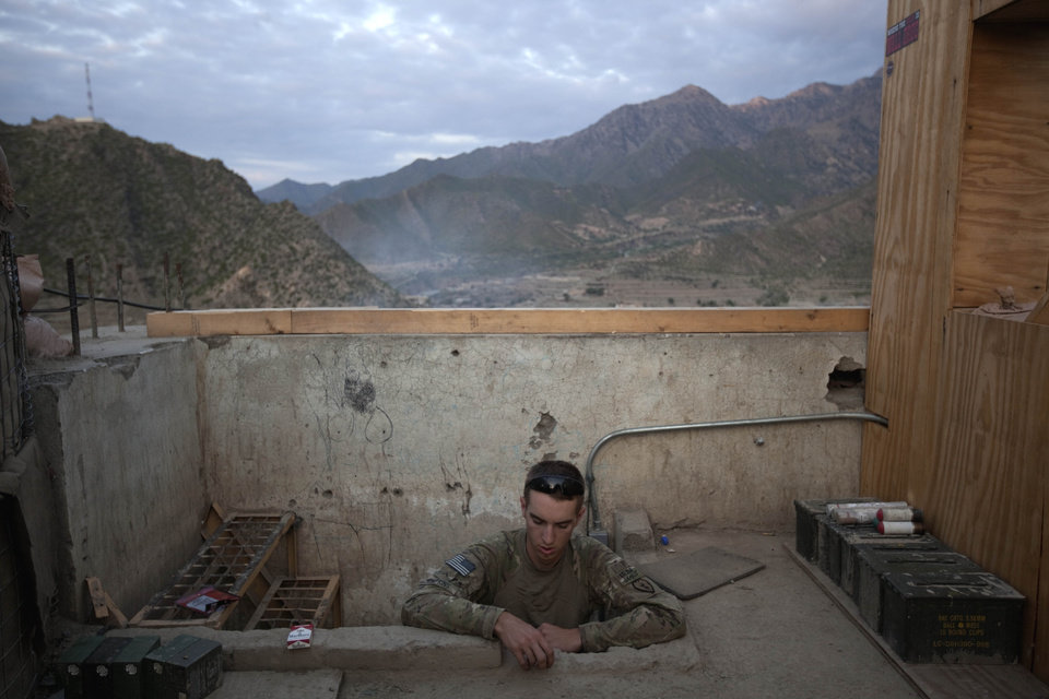 Pfc. Michael Tompkins, 20, of Wadsworth, Ohio, with the U.S. Army's Bravo Company of the 25th Infantry Division, 3rd Brigade Combat Team, 2nd Battalion 27th Infantry Regiment based in Schofield Barracks, Hawaii, pokes his head up to a watchtower at dawn Sunday, Sept. 11, 2011 at Observation Post Coleman in Kunar province, Afghanistan. (AP Photo/David Goldman)