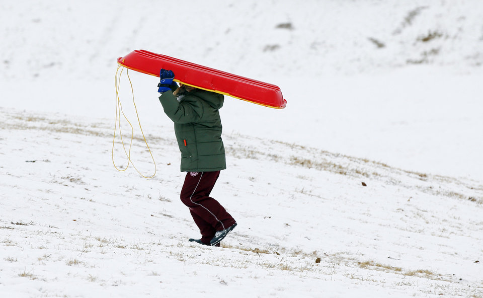 Photo - A sledder walks uphill after a ride at Douglas Park in Oklahoma City, Friday, Jan. 6, 2017. Photo by Nate Billings, The Oklahoman