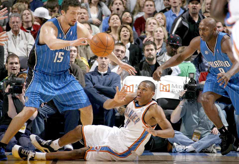 Photo - Oklahoma City's Russell Westbrook passes the ball between Hedo Turkoglu, left, and Anthony Johnson of Orlando during the NBA basketball game between the Oklahoma City Thunder and the Orlando Magic at the Ford Center in Oklahoma City, Wednesday, Nov. 12, 2008. BY BRYAN TERRY, THE OKLAHOMAN   ORG XMIT: KOD