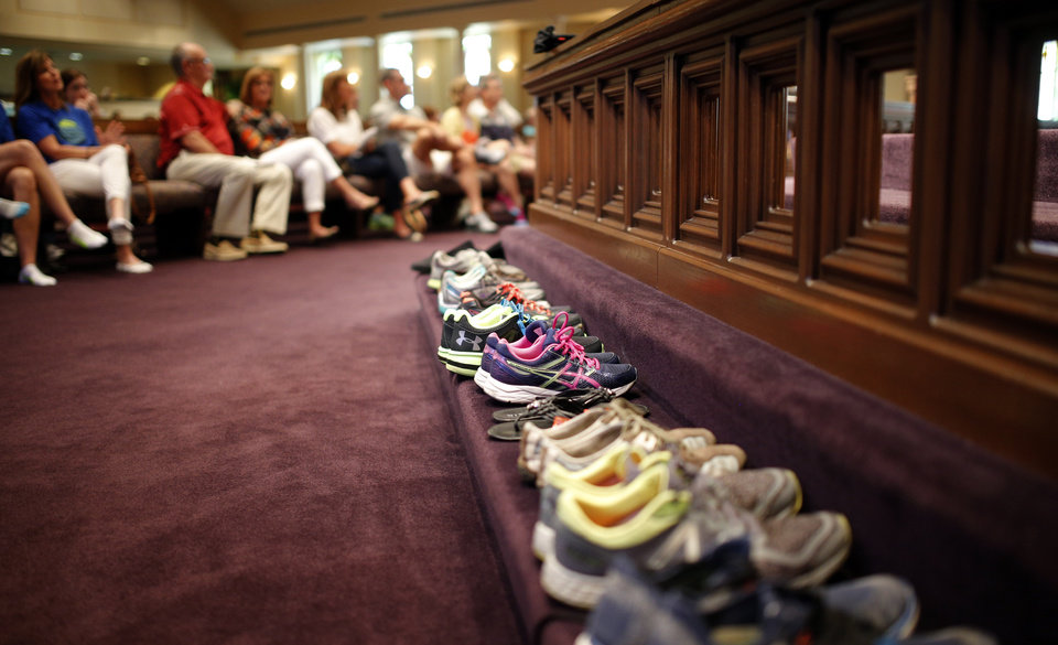 Photo - Shoes sit on the alter during the Blessing of the Shoes service at First Church in downtown Oklahoma City Saturday, April 23, 2016. The service blessed the shoes of those running in the Memorial Marathon Sunday morning. Photo by Sarah Phipps, The Oklahoman