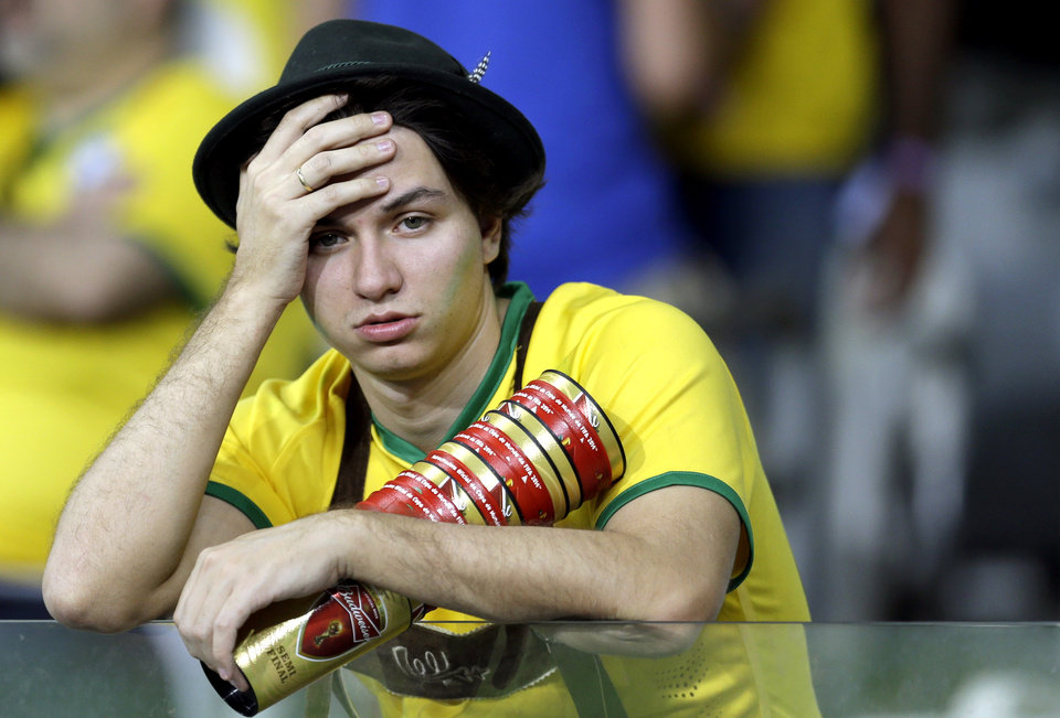 A Brazil supporter reacts after Germany defeated Brazil 7-1 to advance to the finals during the World Cup semifinal soccer match between Brazil and Germany at the Mineirao Stadium in Belo Horizonte, Brazil, Tuesday, July 8, 2014. (AP Photo/Natacha Pisarenko)