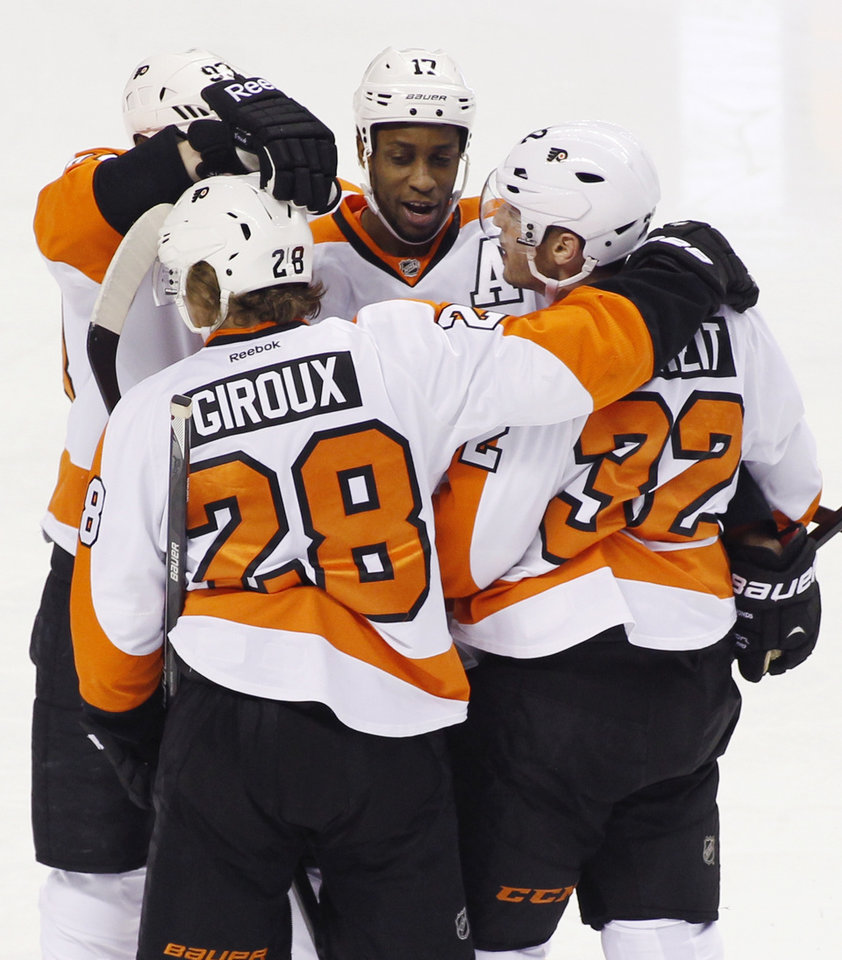 Photo - Philadelphia Flyers' Wayne Simmonds, celebrates with teammates, from left, Jakub Voracek, Claude Giroux (28) and Mark Streit (32) after scoring against the San Jose Sharks during the first period of an NHL hockey game, Monday, Feb. 3, 2014, in San Jose, Calif. (AP Photo/George Nikitin)