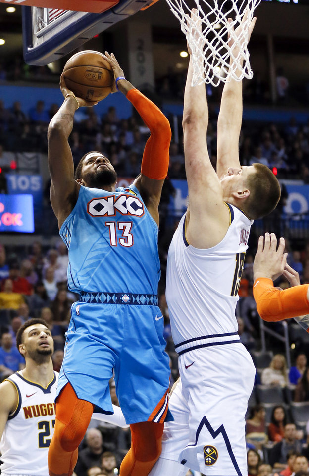 Photo - Oklahoma City's Paul George (13) shoots against Denver's Nikola Jokic (15) in the first quarter during an NBA basketball game between the Denver Nuggets and the Oklahoma City Thunder at Chesapeake Energy Arena in Oklahoma City, Friday, March 29, 2019. Photo by Nate Billings, The Oklahoman