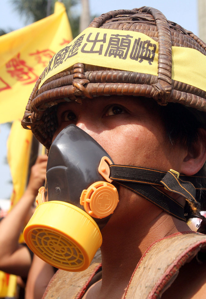 "A protester wears a slogan reading ""Removal nuclear waste stored out of Orchid Island"" during an anti-nuclear demonstration in Taipei, Taiwan, Saturday, March 9, 2013. Tens of thousands of Taiwanese have protested to demand that the government scrap a $10 billion nuclear power plant that is nearly complete and slated to begin operating in two years. (AP Photo/Chiang Ying-ying)"