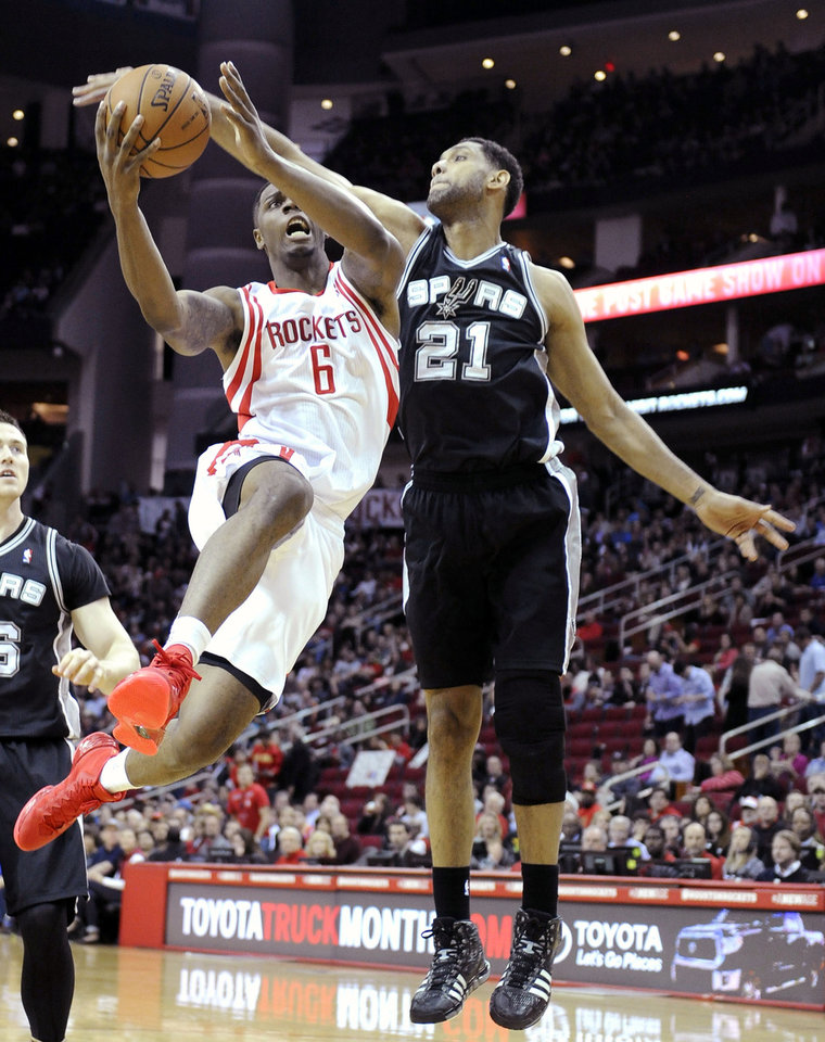 Photo - San Antonio Spurs' Tim Duncan (21) tries to block a shot by Houston Rockets' Terrence Jones (6) in the first half of an NBA basketball game Monday, April 14, 2014, in Houston. (AP Photo/Pat Sullivan)