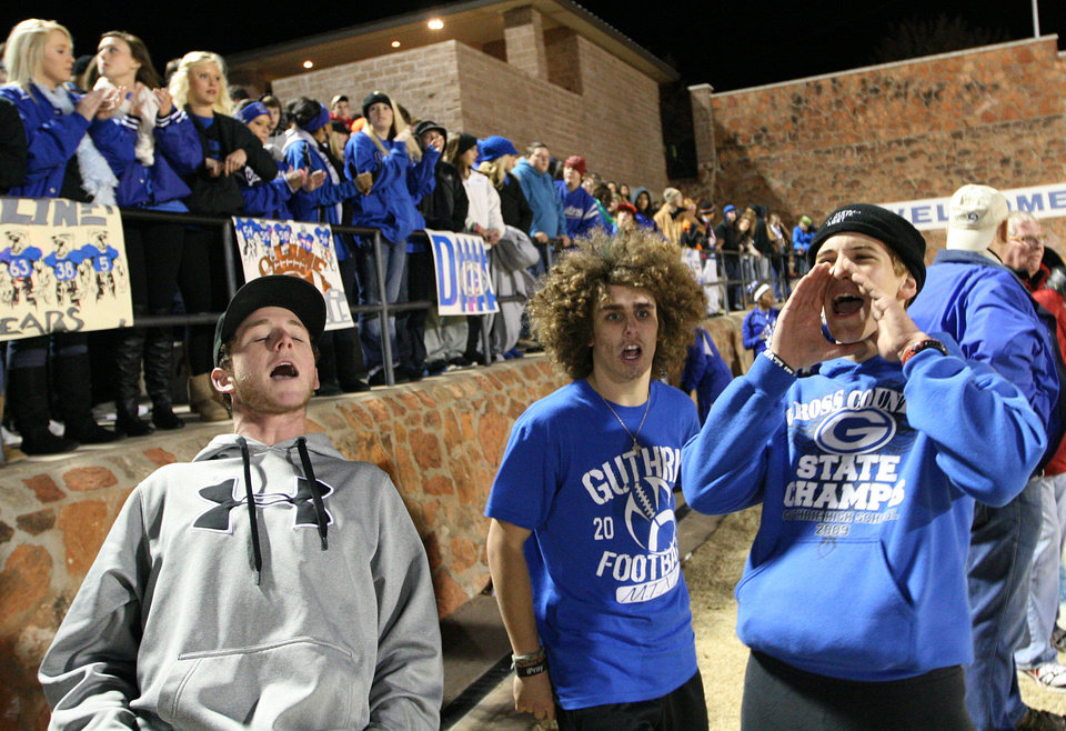 Photo - Sophomore Dylan Harman, junior Joey Pozo, and senior Walker Cross, celebrate on the sidelines during a high school football game between Guthrie and East Central at The Rock in Guthrie, Friday, Nov. 18, 2011.  Photo by Garett Fisbeck, The Oklahoman