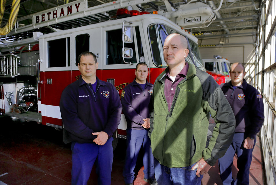 Photo - Bethany Firefighters Aaron Whitfield, Chris Allbritton, Brian Murray and Kyle Freeman, from left, pose for a photo at their station in Bethany on Friday. The department is fighting the firing of firefighter Josh Morgan after the department was awarded a raise through arbitration. Photo by Chris Landsberger, The Oklahoman  CHRIS LANDSBERGER