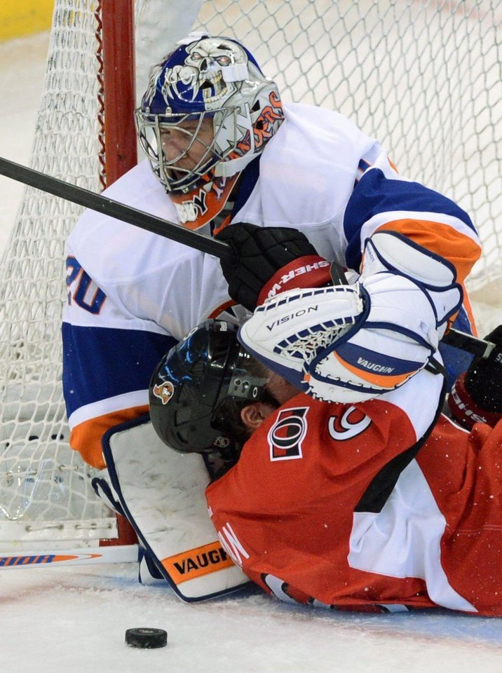 Photo - Ottawa Senators' Bobby Ryan slides into New York Islanders goalie Evgeni Nabokov during the first period of a preseason NHL hockey game in Ottawa, Ontario, on Sunday, Sept. 29, 2013. (AP Photo/The Canadian Press, Sean Kilpatrick)