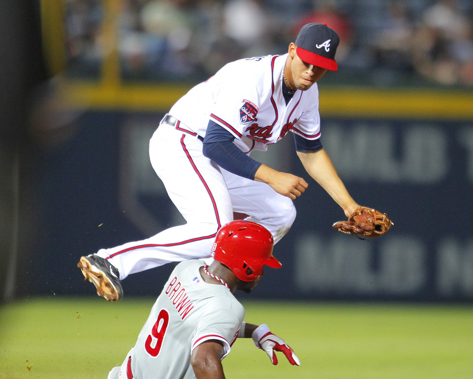 Photo - Atlanta Braves shortstop Andrelton Simmons (19) turns the double play as Philadelphia Phillies Domonic Brown (9) slides into second in the ninth inning of a baseball game Tuesday, June 17, 2014, in Atlanta. (AP Photo/Todd Kirkland)