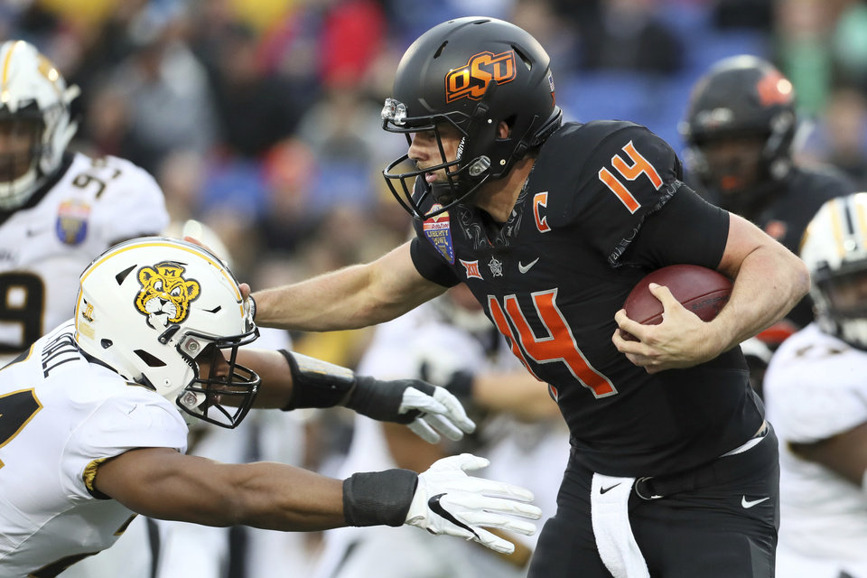 Photo - Oklahoma State quarterback Taylor Cornelius tries to stiff-arm Missouri linebacker Terez Hall during the first half of the Liberty Bowl NCAA college football game in Memphis, Tenn., Monday, Dec. 31, 2018. (Joe Rondone/The Commercial Appeal via AP)