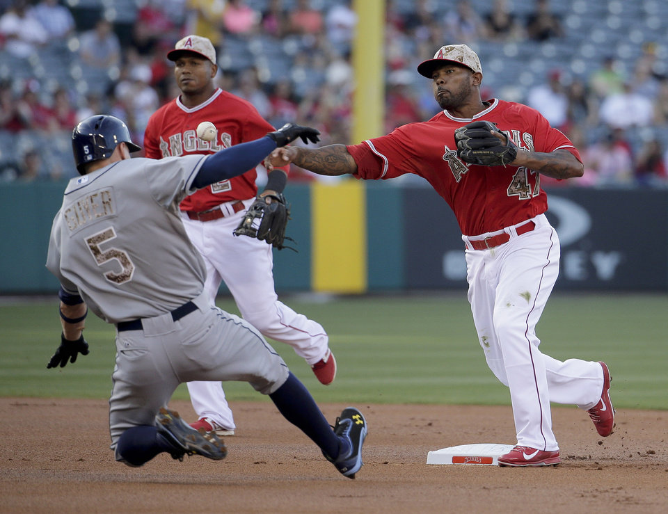 Photo - Tampa Bay Rays' Brandon Guyer, left, slides after being forced out at second by Los Angeles Angels second baseman Howie Kendrick after Wil Myers hit into a double play during the first inning of a baseball game in Anaheim, Calif., Saturday, May 17, 2014. (AP Photo/Chris Carlson)