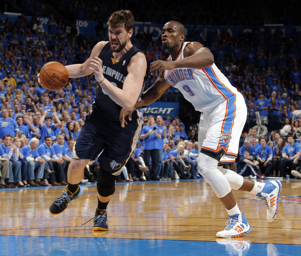 Photo - Memphis' Marc Gasol (33) drives past Oklahoma City 's Serge Ibaka (9) during Game 1 in the first round of the NBA playoffs between the Oklahoma City Thunder and the Memphis Grizzlies at Chesapeake Energy Arena in Oklahoma City, Saturday, April 19, 2014. Photo by Sarah Phipps, The Oklahoman