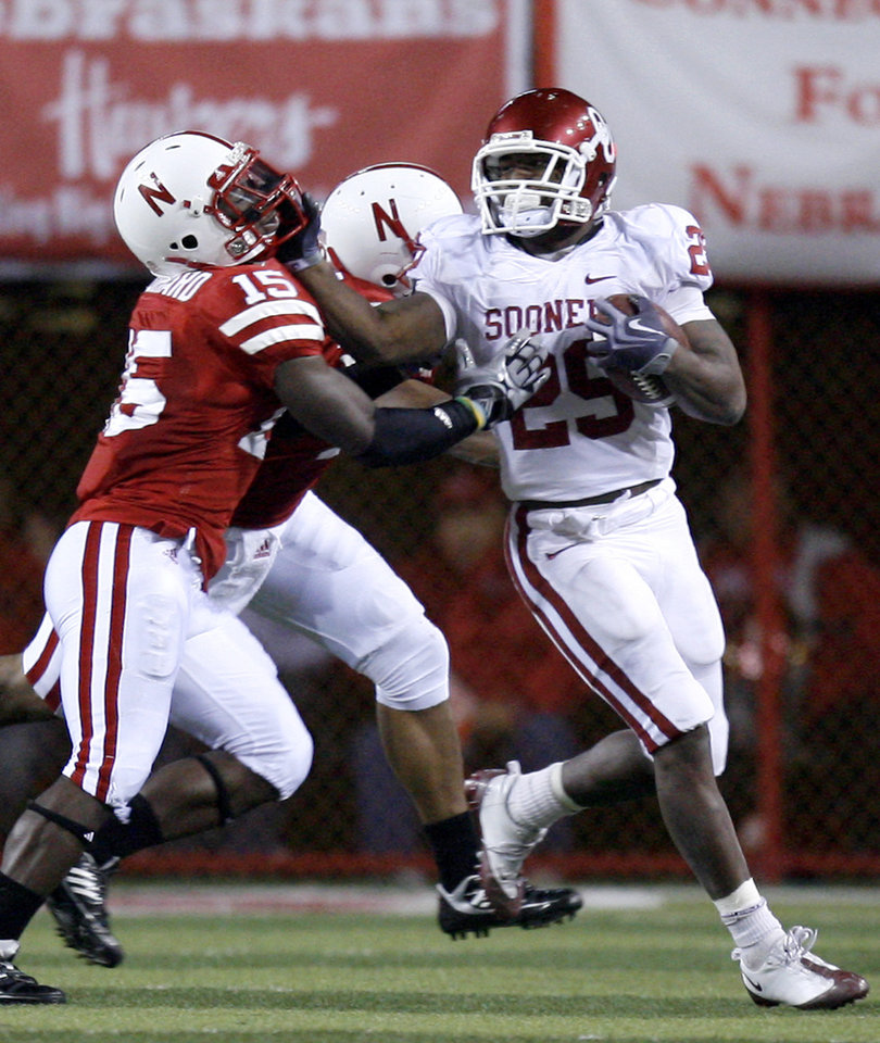 Photo - OU's Chris Brown (29) stiff arms Nebraska's Alfonzo Dennard (15) during the second half of the college football game between the University of Oklahoma Sooners (OU) and the University of Nebraska Cornhuskers (NU) on Saturday, Nov. 7, 2009, in Lincoln, Neb. Photo by Sarah Phipps, The Oklahoman