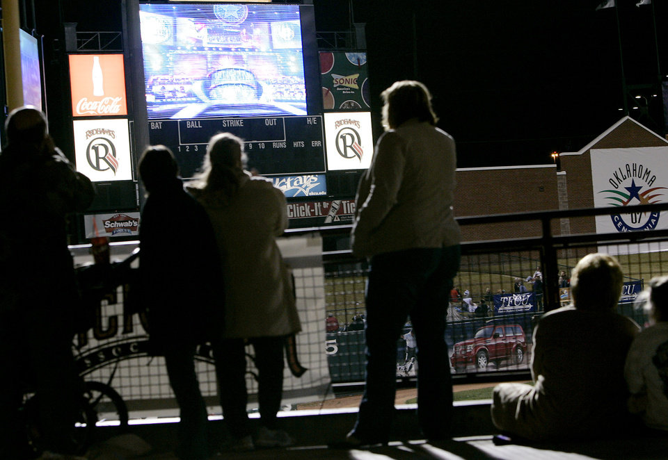 Photo - People stand in the concourse area as they watch the Centennial Spectacular at the AT&T Bricktown Ballpark in Oklahoma City as part of the State's Centennial celebration. By John Clanton, The Oklahoman