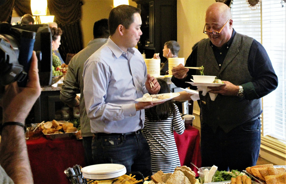 Photo -  Ba Luong, left, and celebrity chef Andrew Zimmern chat during a December shoot in the co-owner of Super Cao Nguyen Market's home. The episode airs Tuesday on Travel Channel. [Photo by Dave Cathey, The Oklahoman]