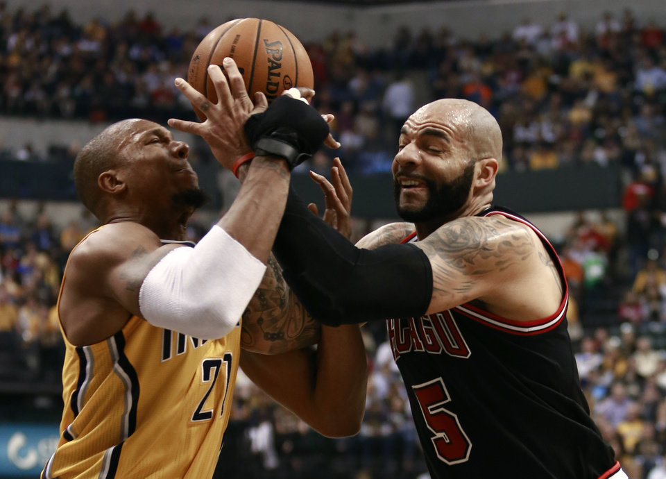 Photo - CORRECTS SPELLING OF BOOZER - Chicago Bulls forward Carlos Boozer, right, competes with Indiana Pacers forward David West for the basketball in the first half of an NBA basketball game in Indianapolis, Friday, March 21, 2014. (AP Photo/R Brent Smith)