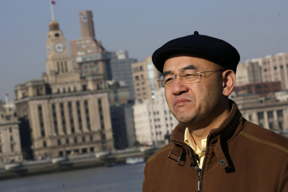 In this Jan. 28, 2013 photo, Chinese-born U.S. scientist Hu Zhicheng stands at the waterfront promenade along the Huangpu River in Shanghai, China. For 17 months he was jailed while police investigated accusations from a business rival. During that time, he and his family say, he was allowed no contact with his wife or children other than the occasional letter. (AP Photo/Eugene Hoshiko)