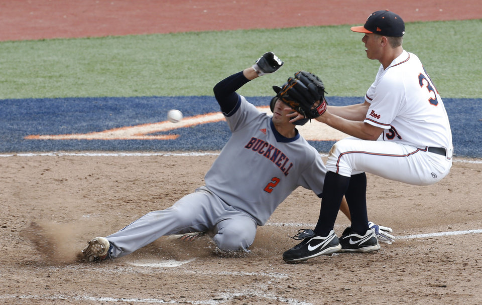 Photo - Bucknell's Brett Smith (2) scores as Virginia pitcher Connor Jones waits for the ball in the eighth inning during an NCAA college baseball tournament regional game in Charlottesville, Va., Friday, May 30, 2014. Virginia won 10-1. Smith scored on a wild pitch.  (AP Photo/Steve Helber)