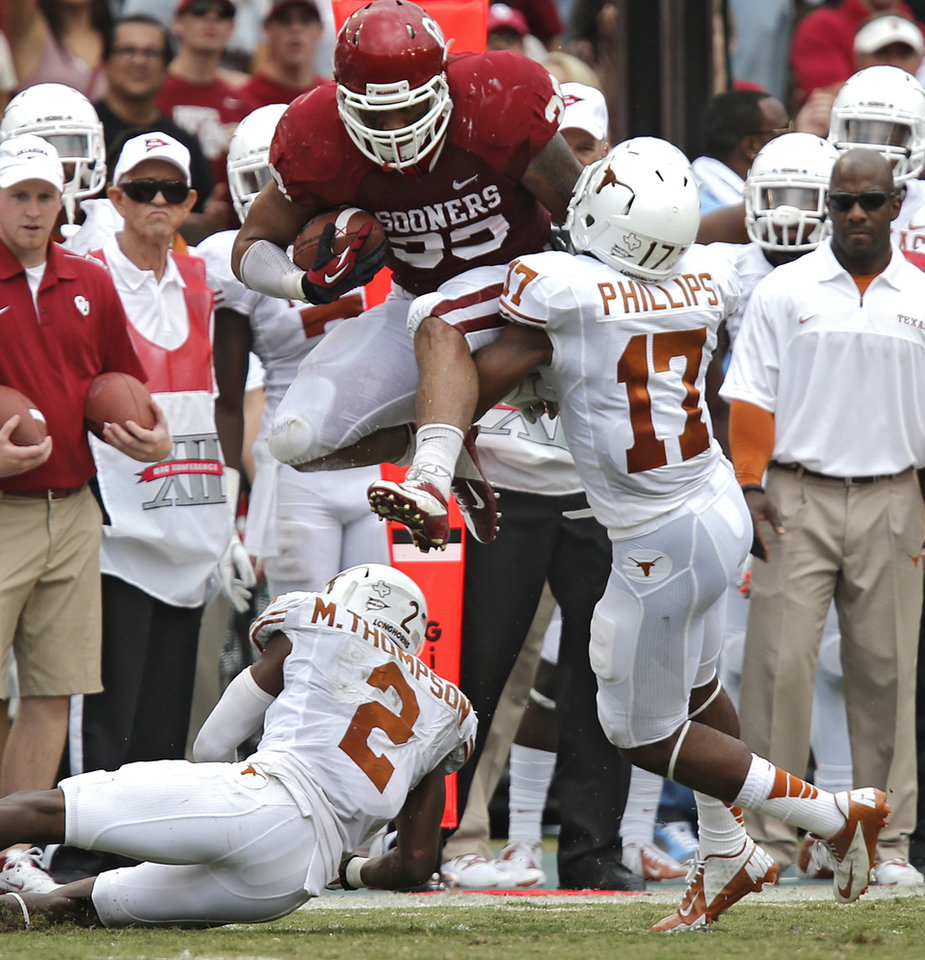 Photo - OU's Trey Millard (33) leaps over UT's Mykkele Thompson (2) and Adrian Phillips (17) during the Red River Rivalry college football game between the University of Oklahoma (OU) and the University of Texas (UT) at the Cotton Bowl in Dallas, Saturday, Oct. 13, 2012. Photo by Chris Landsberger, The Oklahoman