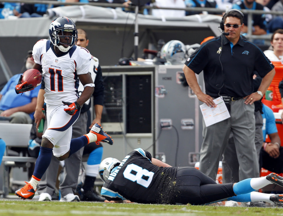 Photo -   Denver Broncos' Trindon Holliday (11) runs past Carolina Panthers' Brad Nortman (8) as he returns a punt for a touchdown during the first half of an NFL football game in Charlotte, N.C., Sunday, Nov. 11, 2012. Carolina Panthers head coach Ron Rivera, right, looks on. (AP Photo/Bob Leverone)