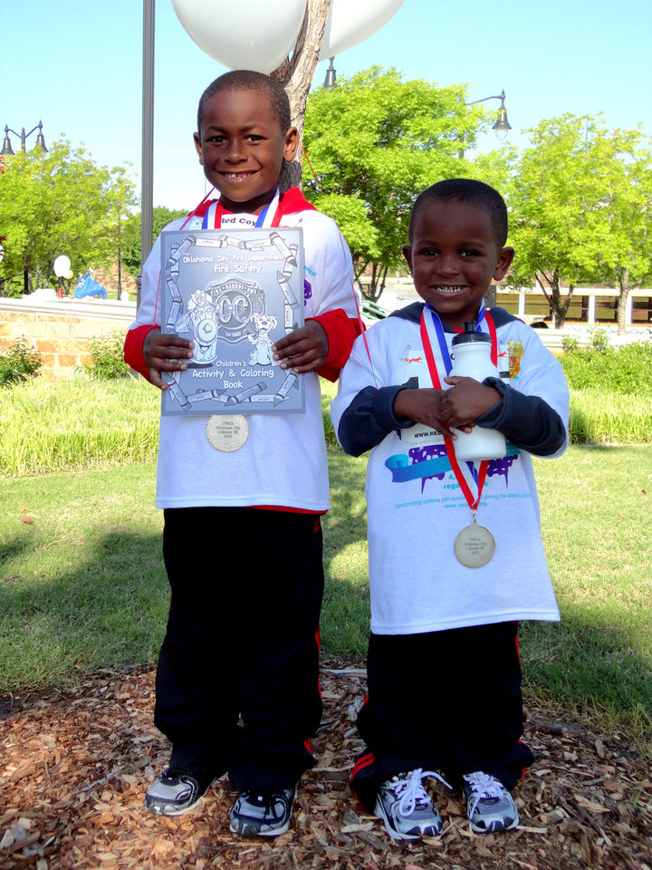 Photo - Treshawn Neal, age 7, left, and brother Tristan Neal, age 3, of Oklahoma City, show off their medals from the YWCA's 2-Minute 5K