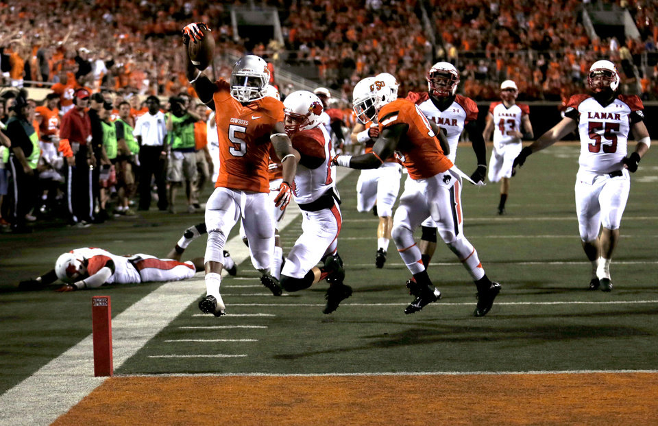 Photo - Oklahoma State's Josh Stewart (5) scores a touchdown on a 67-yard punt return in the third quarter during a college football game between the Oklahoma State University Cowboys (OSU) and the Lamar University Cardinals at Boone Pickens Stadium in Stillwater, Okla., Saturday, Sept. 14, 2013. Photo by Sarah Phipps, The Oklahoman