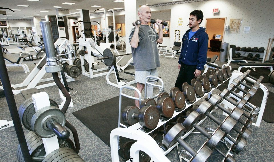 Photo - Norman resident Bill Boettcher works out with trainer Tony Tran in the U.S. Postal Center's gymnasium. PHOTO BY JACONNA AGUIRRE, THE OKLAHOMAN