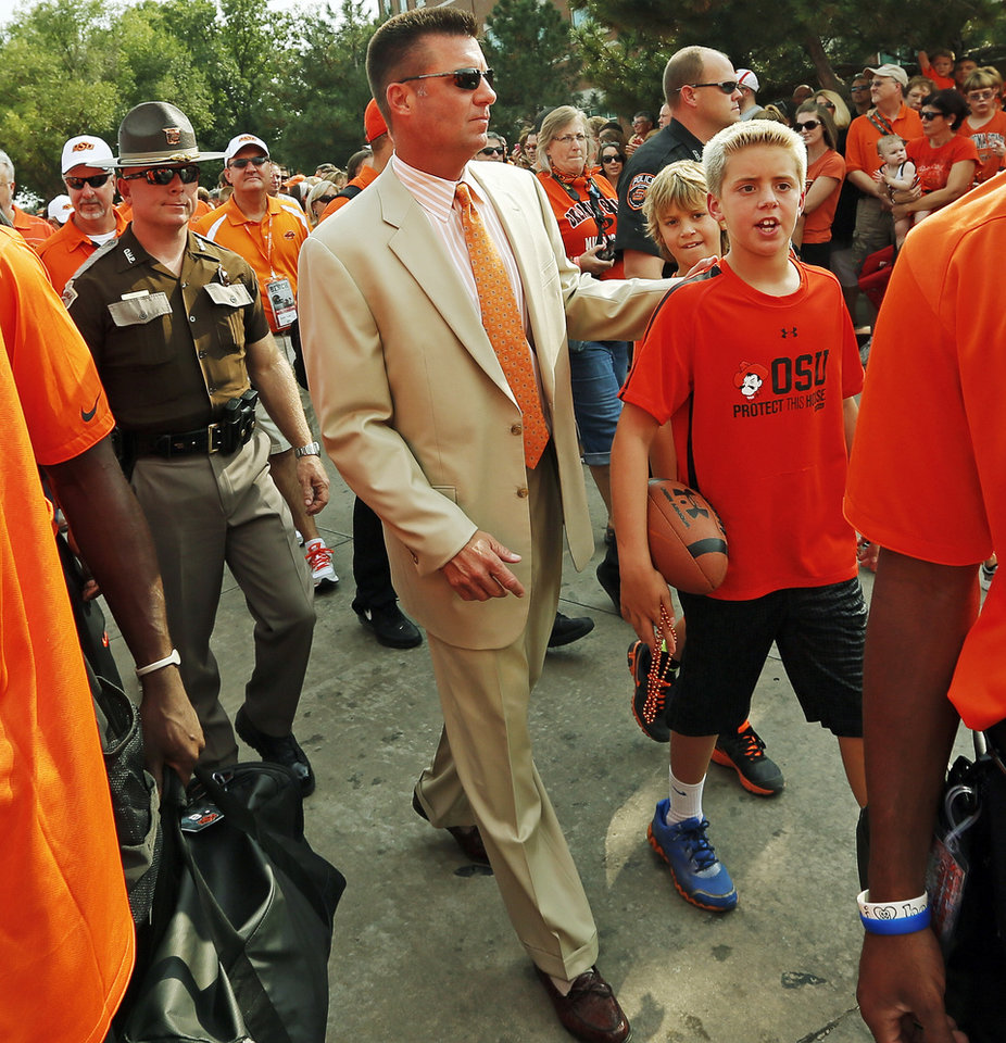 OSU head coach Mike Gundy walks to the stadium with his team during the Spirit Walk before a college football game between the Oklahoma State University Cowboys (OSU) and the Lamar University Cardinals at Boone Pickens Stadium in Stillwater, Okla., Saturday, Sept. 14, 2013. Photo by Nate Billings, The Oklahoman