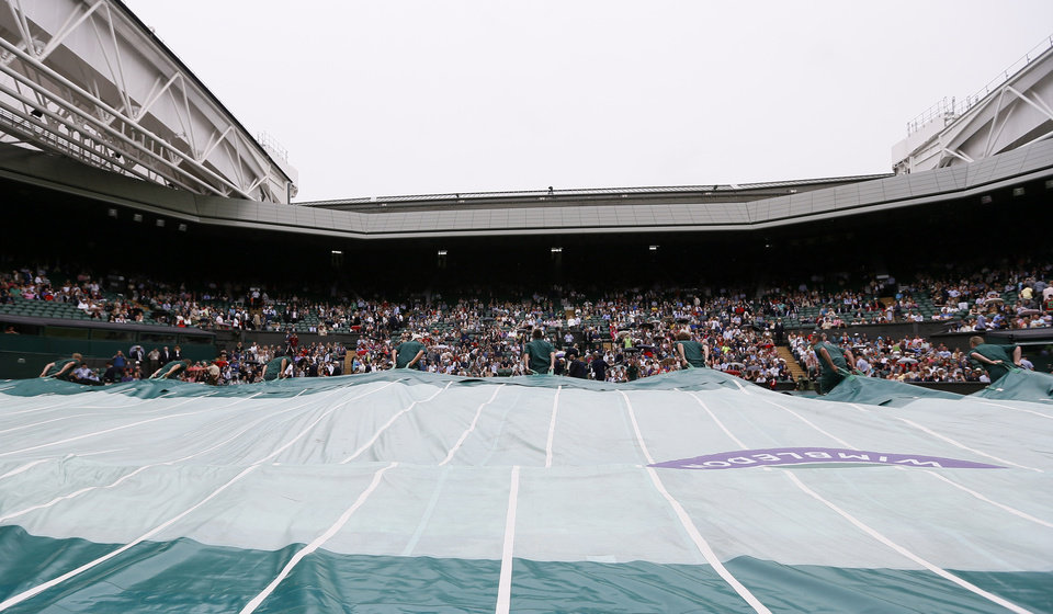The covers go onto Centre Court as rain stopped play during a Women's second round singles match between Agnieszka Radwanska of Poland and Mathilde Johansson of France at the All England Lawn Tennis Championships in Wimbledon, London, Thursday, June 27, 2013. (AP Photo/Kirsty Wigglesworth)