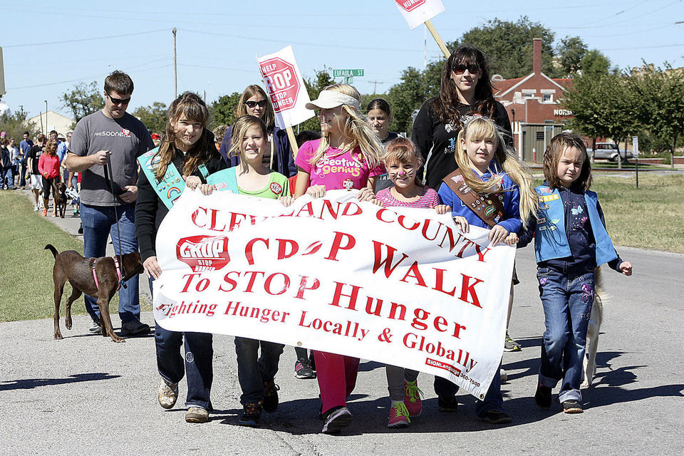 Photo - Norman Girl Scouts lead the way as walkers set out on the annual CROP Walk to Stop Hunger. PHOTO BY LYNETTE LOBBAN, FOR THE OKLAHOMAN