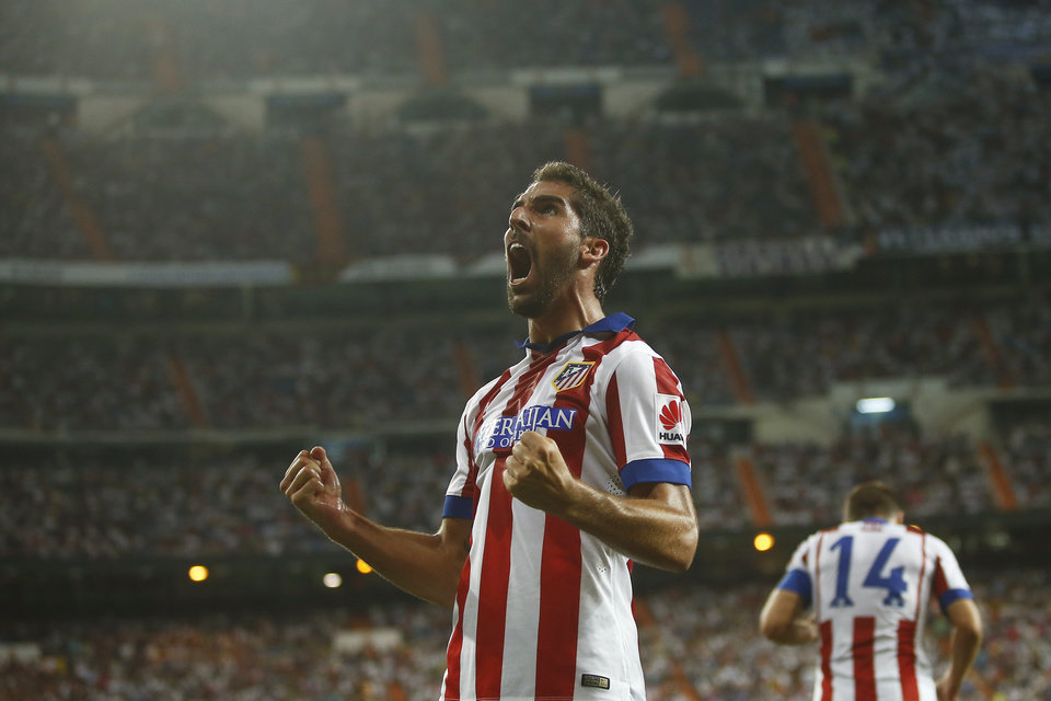 Photo - Atletico's Raul Garcia celebrates his goal during a Spanish Supercup first leg soccer match between Real Madrid and Atletico Madrid at Santiago Bernabeu stadium in Madrid, Spain, Tuesday, Aug. 19, 2014. (AP Photo/Andres Kudacki)