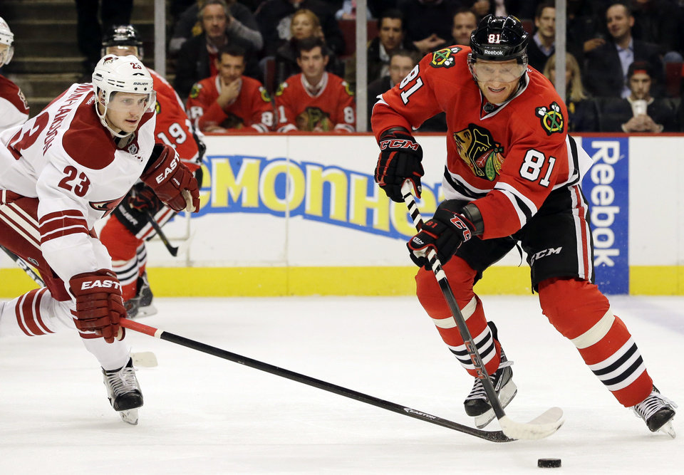Chicago Blackhawks' Marian Hossa, right, controls the puck against Phoenix Coyotes' Oliver Ekman-Larsson during the second period of an NHL hockey game in Chicago, Thursday, Nov. 14, 2013. (AP Photo/Nam Y. Huh)