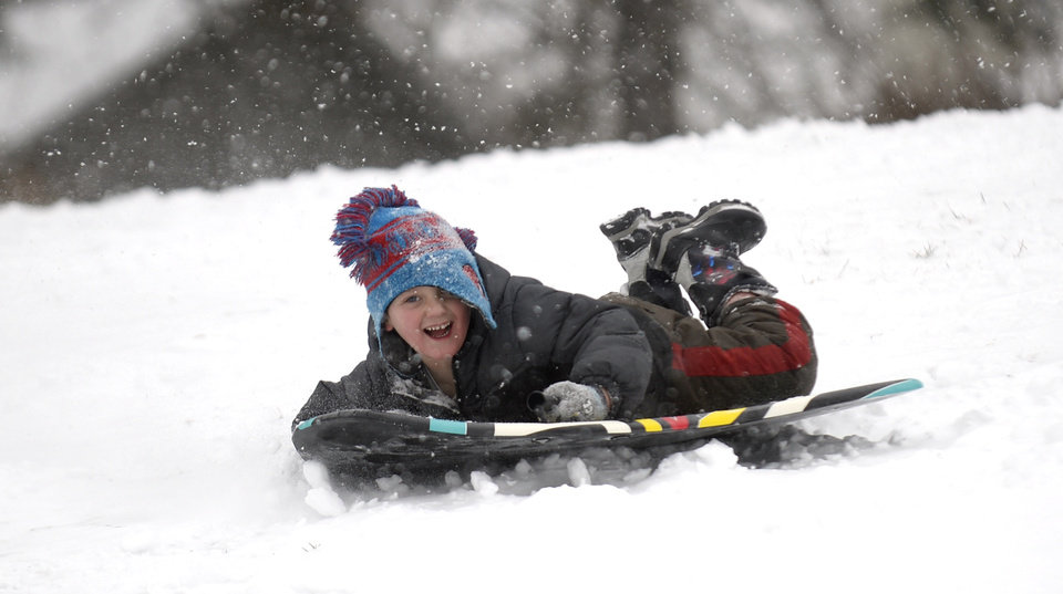 Photo - Eric Weiser, 5, of Lebanon, Pa., sleds down the hill on Tuesday, Jan. 21, 2014, in Lebanon, Pa. The National Weather Service predicts the storm could drop 8 to 12 inches of snow followed by bitterly cold temperatures. (AP Photo/Lebanon Daily News, Jeremy Long)  THE PATRIOT-NEWS OUT
