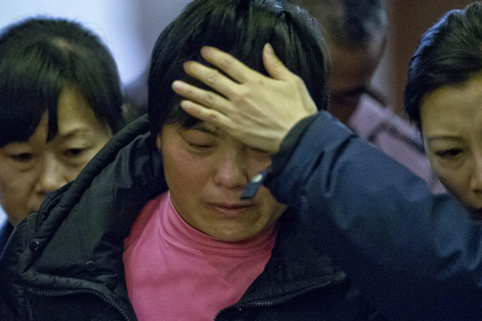 Photo - A crying woman, one of the relatives of Chinese passengers aboard missing Malaysia Airlines Flight MH370, is assisted by volunteers as she leaves a hotel ballroom where families were briefed on rescue and searching efforts in Beijing, China, Friday, March 14, 2014. (AP Photo/Alexander F. Yuan)