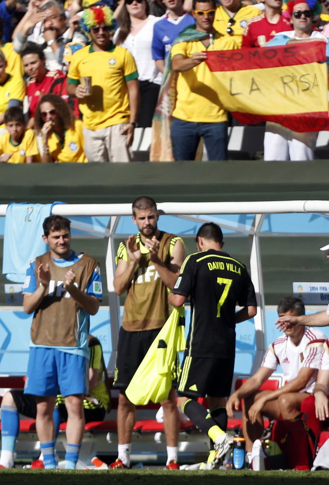 Photo - Spanish players Iker Casillas and Gerard Pique applaud as Spain's David Villa (7), is substituted during the group B World Cup soccer match between Australia and Spain at the Arena da Baixada in Curitiba, Brazil, Monday, June 23, 2014.  (AP Photo/Jon Super)
