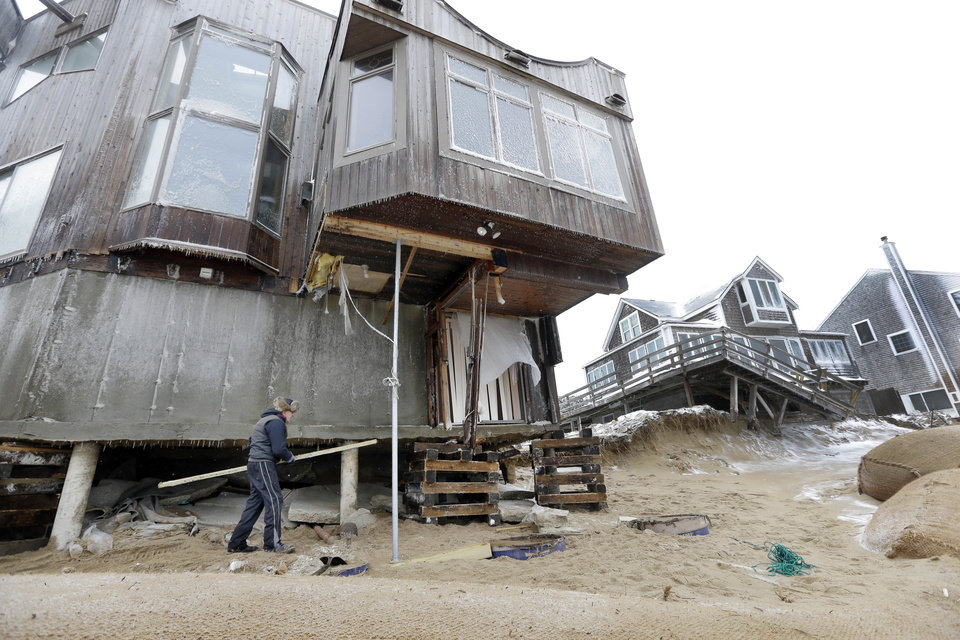 Tom Nee carries wood to shore up his damaged home on Plum Island in Newbury Mass., Saturday, Feb. 9, 2013. A behemoth storm packing hurricane-force wind gusts and blizzard conditions swept through the Northeast on Saturday, dumping more than 2 feet of snow on New England and knocking out power to 650,000 homes and businesses. (AP Photo/Elise Amendola)