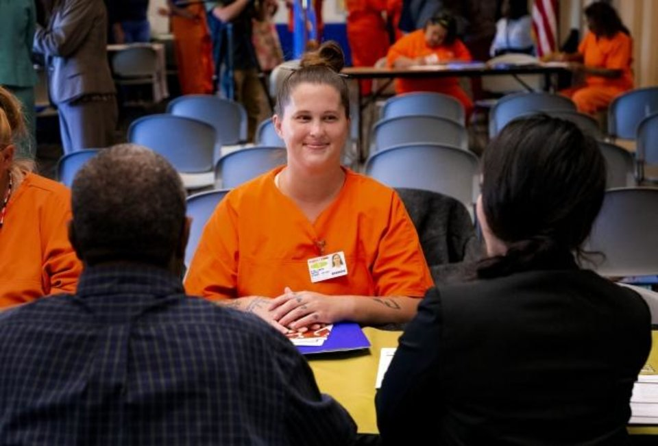 Photo - Inmate Amanda Stallings speaks with a non profit organization during a Transition Fair at Kate Barnard Correctional Center in Oklahoma City, Okla. on Monday, Oct. 14, 2019. The event is part of dozens across the state featuring representatives from area nonprofits, connecting inmates nearing release or up for commutation due to HB 1269 with services to re-integrate successfully into society after prison.[Chris Landsberger/The Oklahoman]