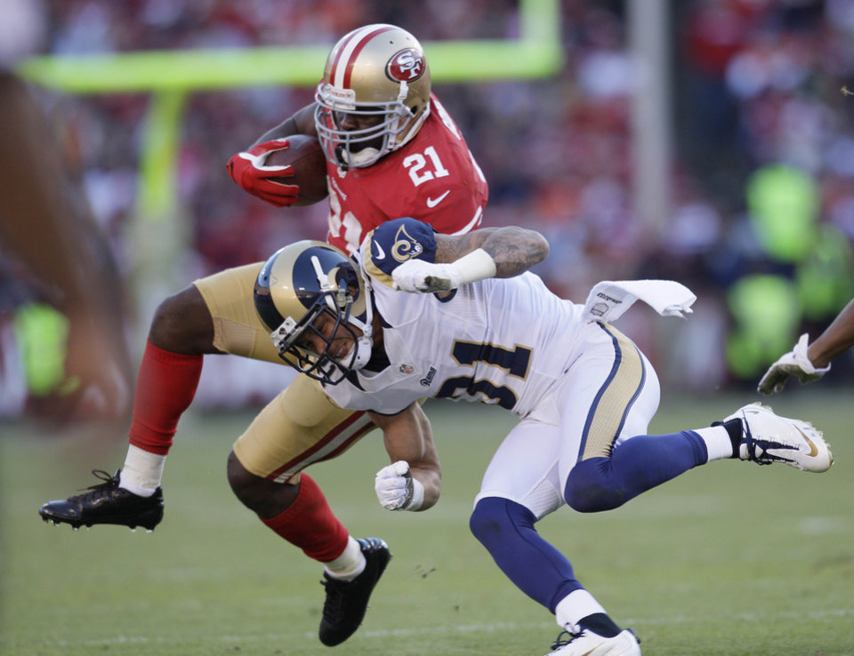 San Francisco 49ers running back Frank Gore runs with the ball and is hit by St. Louis Rams cornerback Cortland Finnegan during the fourth quarter of an NFL football game in San Francisco, Sunday, Nov. 11, 2012. (AP Photo/Jeff Chiu)