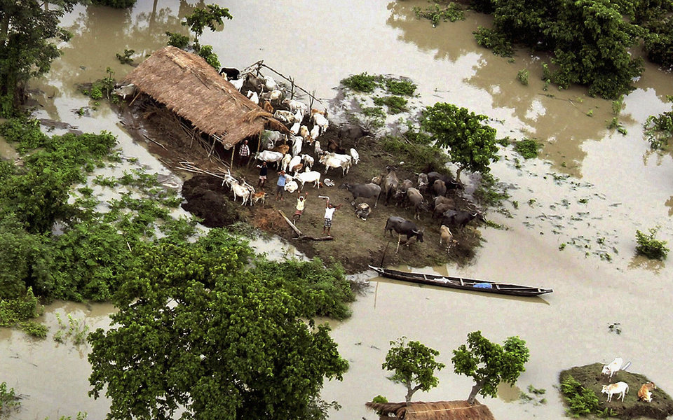 Photo -   Stranded villagers wave to a helicopter as they wait to get rescued in Tezpur, India, Sunday, July 1, 2012. The floods from monsoon rains in northeastern India killed dozens of people, with more than 2,000 villages inundated as rivers breached their banks, an official said Sunday. (AP Photo)