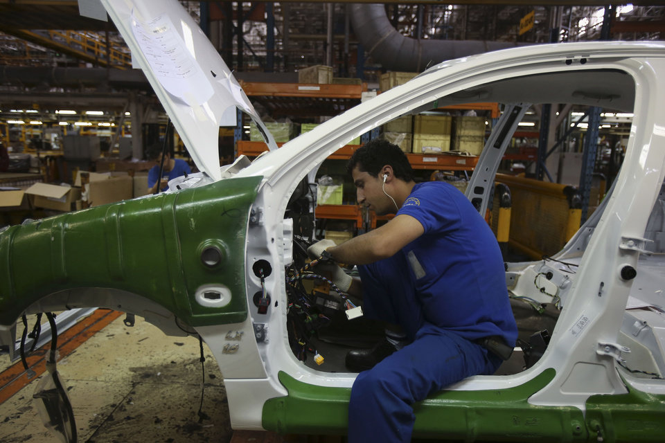 Photo - An Iranian car worker assembles a car at the state-run Iran-Khodro automobile manufacturing plant near Tehran, Iran, Sunday, June 29, 2014. Iran began exporting automobiles to Russia for the first time in five years on Sunday, after meeting upgraded emission standards, the country's largest auto manufacturer said. (AP Photo/Vahid Salemi)