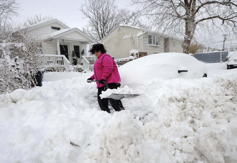 April Palmieri digs out her car in front of her home, background left, on 17th Street after a snow storm on Saturday, Feb. 9, 2013 in Bayville, N.Y. Palmieri had five feet of water in her basement as result of the rains from Superstorm Sandy. A howling storm across the Northeast left the New York-to-Boston corridor shrouded in 1 to 3 feet of snow Saturday, stranding motorists on highways overnight and piling up drifts so high that some homeowners couldn't get their doors open. More than 650,000 homes and businesses were left without electricity. (AP Photo/Kathy Kmonicek) ORG XMIT: NYKK115