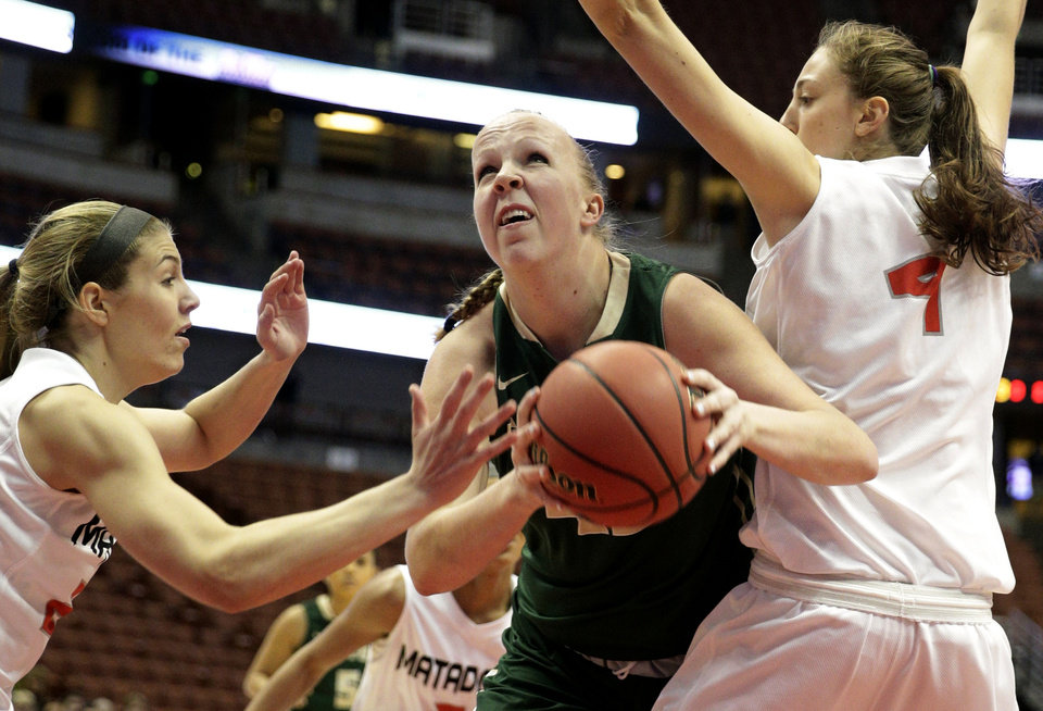 Photo - Cal Poly's Molly Schlemer, center, is defended by Cal State Northridge's Randi Friess, left, and Camille Mahlknecht during the first half of an NCAA college basketball game in the final of the Big West Conference tournament, on Saturday, March 15, 2014, in Anaheim, Calif. (AP Photo/Jae C. Hong)