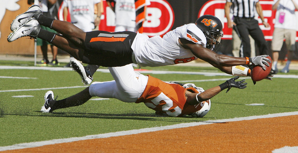 Photo - Oklahoma State's Justin Blackmon (81) dives past Texas' Carrington Byndom (23) for a touchdown in the second quarter during a college football game between the Oklahoma State University Cowboys (OSU) and the University of Texas Longhorns (UT) at Darrell K Royal-Texas Memorial Stadium in Austin, Texas, Saturday, Oct. 15, 2011. Photo by Nate Billings, The Oklahoman
