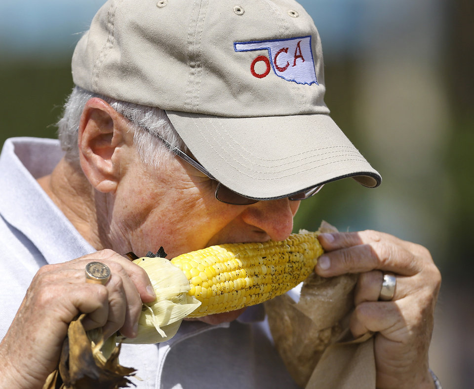 Photo - A man eats a cob of hot roasted corn at the Oklahoma State Fair on Wednesday, , Sep. 18, 2013. Photo  by Jim Beckel, The Oklahoman.