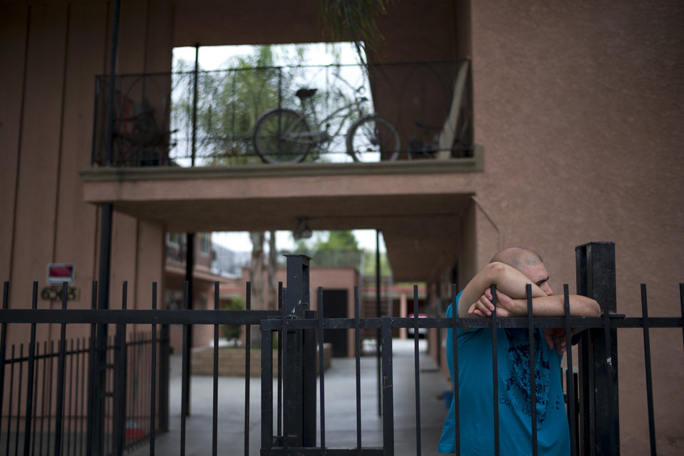 Photo - Frank Tamayo, a manager at an apartment building where suspect Isidro Garcia lived, leans on the fence as he talks with a man from the neighborhood on Thursday, May 22, 2014, in Bell Gardens, Calif. A woman who disappeared a decade ago as a 15-year-old reunited recently with her mother, who convinced her to go to authorities to report that she had been kidnapped and raped by Garcia who is now her husband and father of her daughter. (AP Photo/Jae C. Hong)