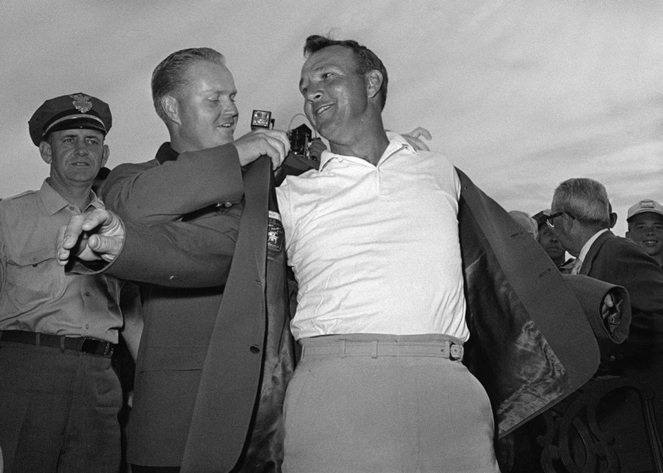 Photo - FILE - In this April 12, 1964 file photo, Arnold Palmer, right, slips into his green jacket with help from Jack Nicklaus after winning the Masters golf championship, in Augusta, Ga.  Fifty years ago, Palmer won the Masters for the fourth time. It was his seventh major. He was 34, the King. (AP Photo/File)