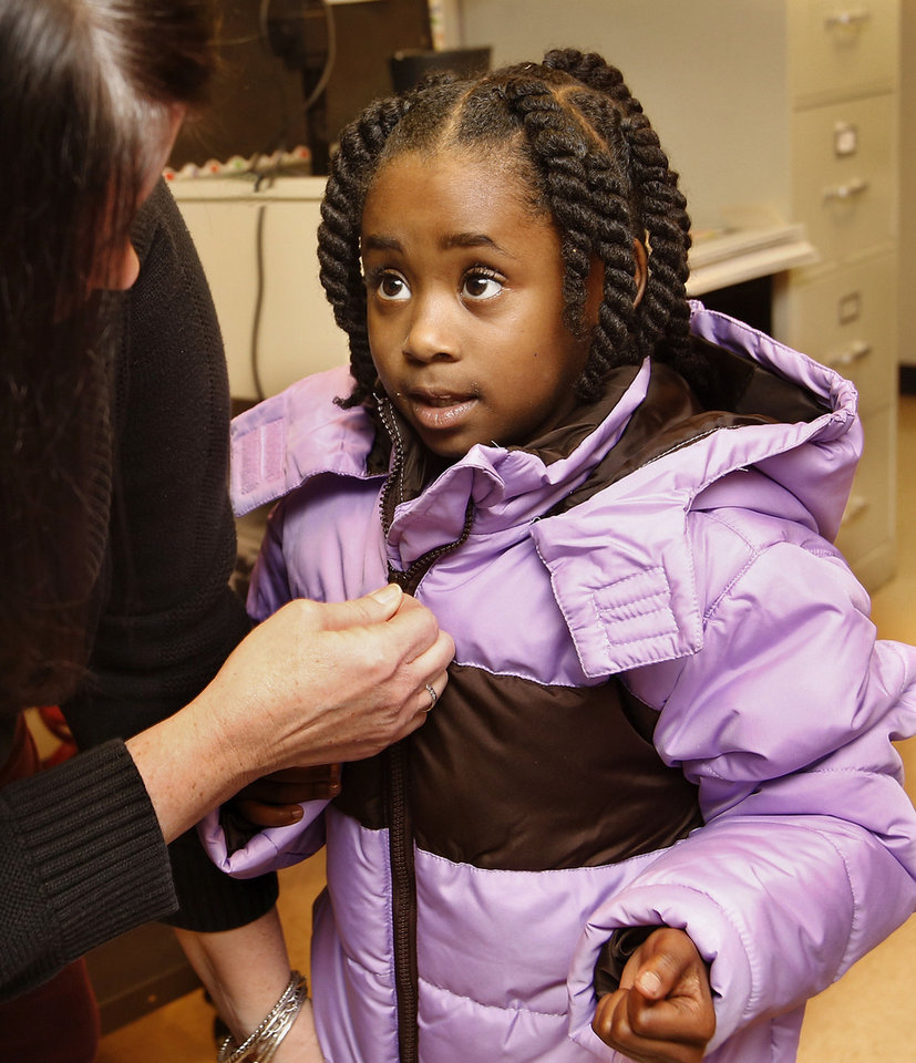 Samiah Logan, a first grader, lets teacher Jennifer Rader zip her new jacket Monday afternoon at Southern Hills Elementary. About 2,000 children in Oklahoma City Public Schools will receive new coats from a national nonprofit called Operation Warm. Jim Beckel - THE OKLAHOMAN